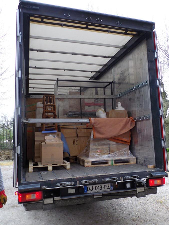 le camion est rempli d'objets divers ( malles en bois, tableaux )